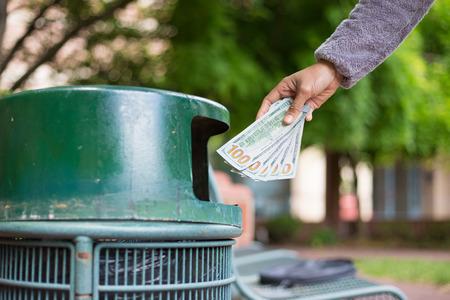 cash money: Primer retrato recortada de alguien que sacude la mano billetes de dólares en efectivo de dinero, billetes de cien dólares en el bote de basura, aislados al aire libre árboles verdes. Malo concepto decisiones de inversión financiera Foto de archivo