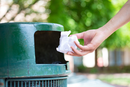 Closeup cropped portrait of someone tossing crumpled piece of paper in trash can, isolated outdoors green trees  Stock Photo