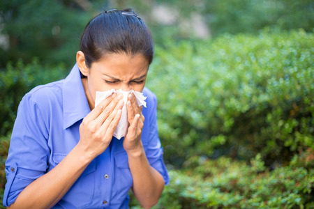 sneeze: Closeup portrait, young woman in blue shirt with allergy or cold, blowing her nose with a tissue, looking miserable unwell very sick, isolated outside green trees . Flu season, vaccination.
