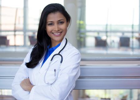doctores: Primer retrato de amable, sonriente mujer m�dico conf�a, profesional con bata de laboratorio y un estetoscopio de la salud, los brazos cruzados. Visita del paciente. La reforma de salud. Foto de archivo