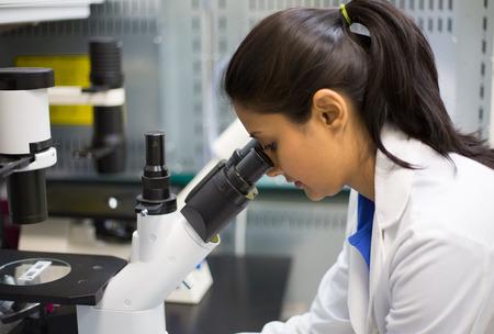 근접 촬영 초상화, 젊은 과학자가 현미경을 찾고. 격리 된 실험실. 연구 및 개발.