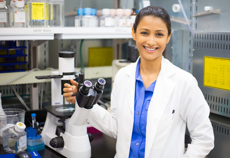 Closeup portrait, young healthcare professional in white lab coat standing beside microscope, smiling. Isolated laboratory . Research and development.
