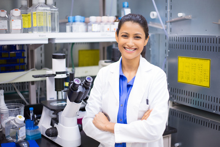 latina girl: Closeup portrait, young smiling scientist in white lab coat standing by microscope. Isolated lab . Research and development.