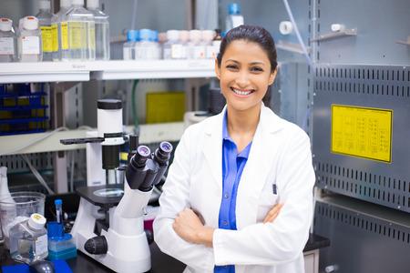 forschung: Großansicht Porträt, junge lächelnde Wissenschaftler im weißen Labormantel stehend von Mikroskop. Isoliert Labor. Forschung und Entwicklung.