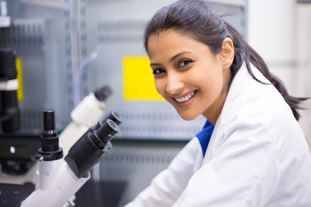 Closeup portrait, young scientist looking into microscope. Isolated lab . Research and development.