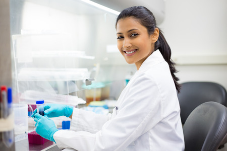 forensics: Closeup portrait, scientist holding 50 mL conical tube with blue liquid solution, laboratory experiments, isolated lab . Forensics, genetics, microbiology, biochemistry Stock Photo