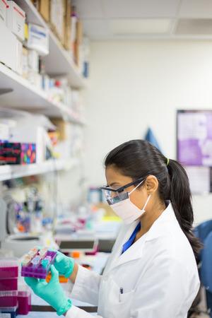 Close-up portret, jonge wetenschapper in witte labjas en een veiligheidsbril en een masker doet experimenten in het lab, de academische sector.