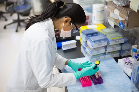 Close-up portret, jonge wetenschapper in witte labjas en veiligheidsbril en masker doet experimenten in het lab, de academische sector. Stockfoto