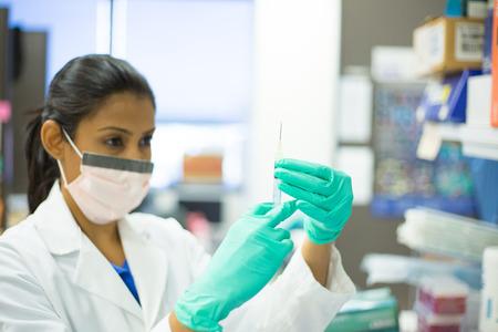 laboratorio clinico: Primer retrato, cient�fico de la mujer inteligente en bata blanca, con la mascarilla, sosteniendo la aguja de la jeringa y agitando, fondo aislado laboratorio
