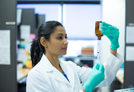 clinical: Closeup portrait, smart woman scientist in white labcoat holding syringe needle and brown bottle in isolated lab background