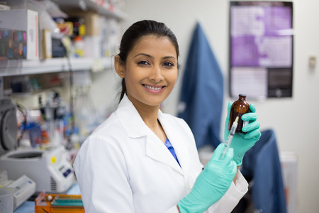 Closeup portrait, smart woman scientist in white labcoat holding syringe needle and brown bottle in isolated lab background