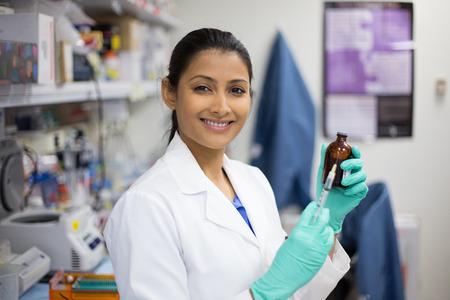 Primer retrato, científico mujer inteligente en la bata blanca que sostiene la jeringa con aguja y la botella de color marrón en el fondo aislado laboratorio Foto de archivo