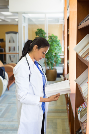 Closeup portrait, woman healthcare professional with stethoscope enjoying reading, studying in library room photo