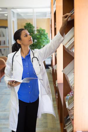 estudiantes medicina: Primer retrato, mujer profesional con el estetoscopio disfrutar de la lectura, el estudio en la sala de la biblioteca de la salud Foto de archivo
