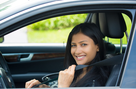 Closeup portrait young smiling, happy, attractive woman pulling on seatbelt inside black car. Driving safety, buckle up to prevent traffic death from accidents concept. Life-saving measures