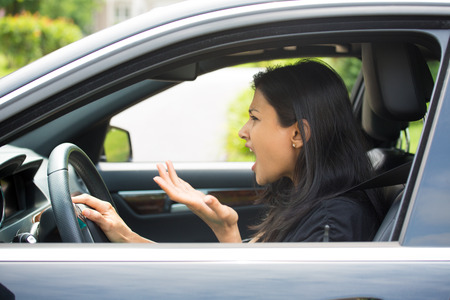 aggressive people: Closeup portrait, angry young sitting woman pissed off by drivers in front of her and gesturing with hands, isolated city street . Road rage traffic jam concept.