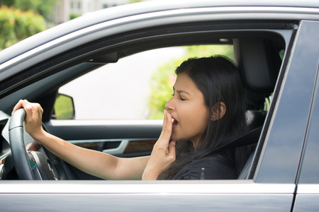 Closeup portrait tired young attractive woman with short attention span, driving her car after long hours trip, yawning at wheel, isolated outside . Sleep deprivation Standard-Bild