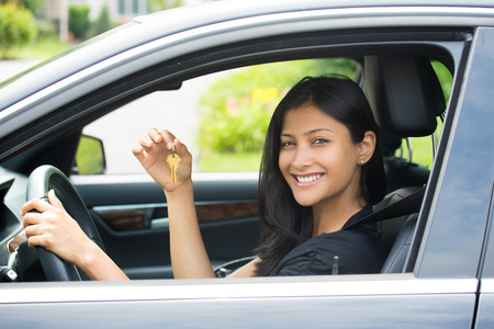 woman driving car: Closeup portrait, young cheerful, joyful, smiling, gorgeous woman holding up keys to her first new car. Customer satisfaction