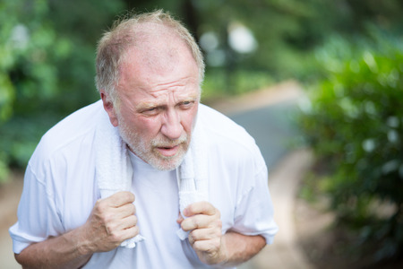 breathlessness: Closeup portrait, senior guy holding towel, very tired, exhausted from over exertion, sun stroke, isolated outdoors outside green trees background