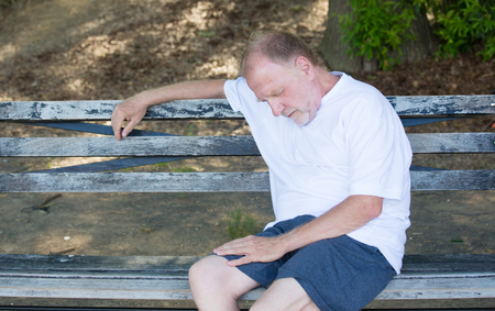 Closeup portrait bald old man in white shirt, blue shorts, exhausted, resting on a bench, looking down, trying to take a power nap, isolated outdoor outside background photo
