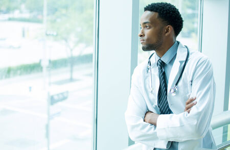 folding arms: Closeup portrait, young healthcare professional, folding arms crossed, daydreaming looking outside, isolated indoors hospital clinic background