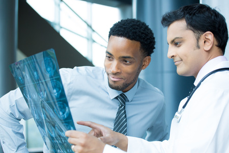 ct scan: Closeup portrait of intellectual healthcare professionals with white labcoat, looking at full body x-ray radiographic image, ct scan, mri, isolated hospital clinic background Stock Photo