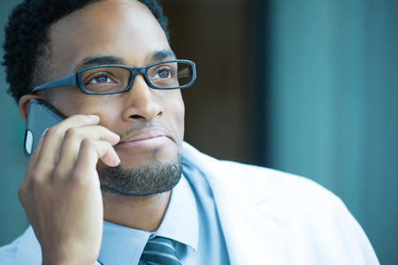 Closeup portrait, friendly, young smiling confident male doctor, healthcare professional talking on phone, isolated indoor clinic hospital background. Patient visit, good news. Positive emotion photo