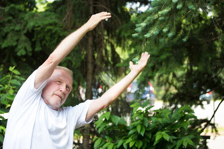 geriatric: Closeup portrait, senior mature man in white shirt, stretching arms, isolated green trees background. Warming up Stock Photo
