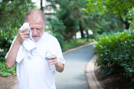 electrolytes: Closeup portrait, old gentleman in white shirt having difficulties with extreme heat, high temperature, wiping sweat from face, very tired, isolated green trees paved road background Stock Photo