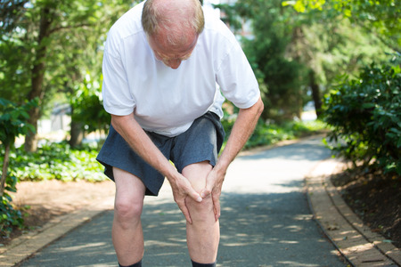 knee joint: Closeup portrait, older man in white shirt, gray shorts, standing on paved road, in severe knee pain, isolated trees outside outdoors background. Stock Photo