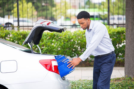 Closeup portrait of a young man trying to fit his luggage in the trunk space, back of his brand new silver car, heavy, blue bag, at a parking lot, side of the road, isolated outdoor background. Stock Photo