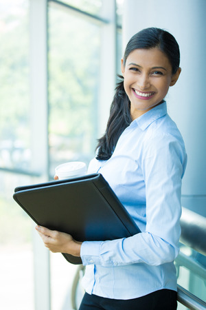 Closeup portrait, young professional, beautiful confident woman in blue shirt, holding coffee and black notebook, smiling isolated indoors office background. Positive human emotions Stockfoto
