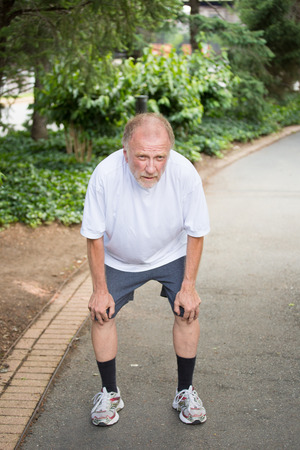 Closeup portrait, old gentleman in white shirt having difficulties with extreme heat, high temperatures, very tired, panting, hands on knees, isolated green trees paved road background. Out of shape