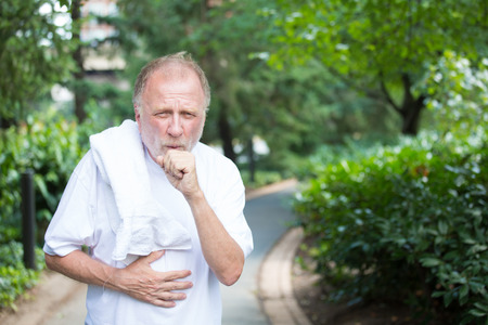 Closeup portrait, old gentleman in white shirt with towel, coughing and holding stomach, isolated green trees and shrubs, outside outdoors background