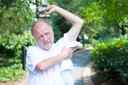 perspiration: Closeup portrait, old gentleman in white shirt wiping sweat droplets dry from body on a hot, sunny, high temperature day, isolated green trees and shrubs background
