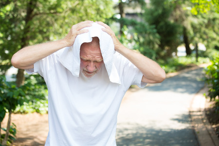 Closeup portrait, old gentleman in white shirt having difficulties with extreme heat, high temperatures, very tired, holding towel over head as shade, isolated green trees paved road background