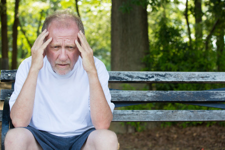 Closeup portrait, stressed older man in white shirt, hands on head with bad headache, sitting on bench, isolated background of trees outside.