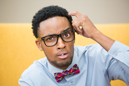 Closeup portrait, young befuddled, bewildered computer geek with big black glasses and bow tie, scratching head wondering about something. Stockfoto