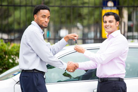 Closeup portrait of handsome young businessman buying a brand new electric car from a salesman, handing over the key, happiness, isolated outdoor background. Positive human emotions