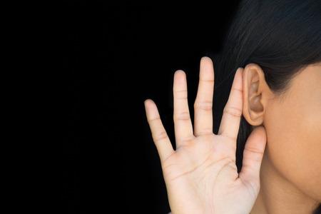 oido: Primer retrato recortada, media cara con el pelo negro, la mano al o�do, escuchando algo, aislado fondo negro. Spies, el espionaje y los esc�ndalos. Palabra en la calle Foto de archivo