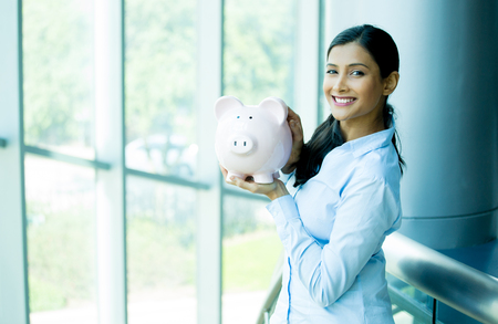 Closeup portrait happy, smiling business woman, holding pink piggy bank, isolated indoors office background. Financial budget savings, smart investment concept photo