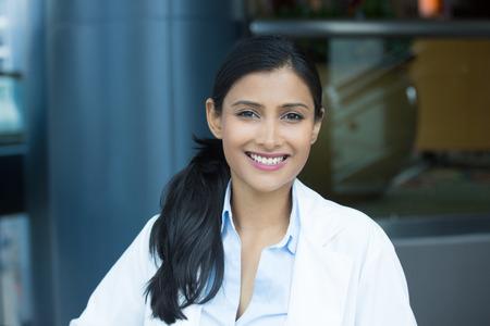 확대 사진 얼굴 만 친절한, 웃는 자신감을 여성, 의료 전문가 실험실 코트 함께 초상화. 격리 된 병원 병원 배경입니다. 환자 방문.