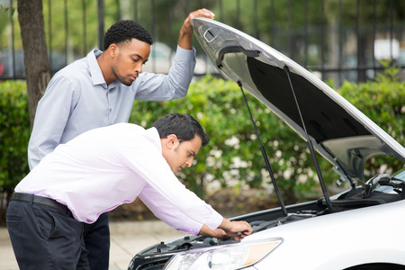 Roadside assistance.  Closeup portrait, two frustrated guys trying to figure out how to fix broken down car on side of road, isolated green trees background