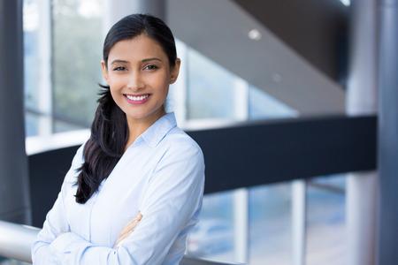 Close-up portret, jonge professionele, mooie zelfverzekerde vrouw in blauw shirt, armen gekruist gevouwen, lacht geïsoleerd binnen kantoor achtergrond. Positieve menselijke emoties