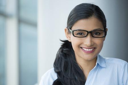 Closeup portrait, jeune professionnel, belle femme adulte confiante en chemise bleue, avec des lunettes noires, souriant isolé fond de bureau à l'intérieur. Émotions humaines positives Banque d'images