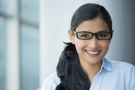 Closeup portrait, young professional, beautiful confident adult woman in blue shirt, with black glasses, smiling isolated indoors office background. Positive human emotions