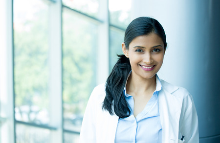 Closeup head shot portrait of friendly, cheerful, smiling confident female, healthcare professional with lab coat. isolated clinic hospital background. Patient visit.