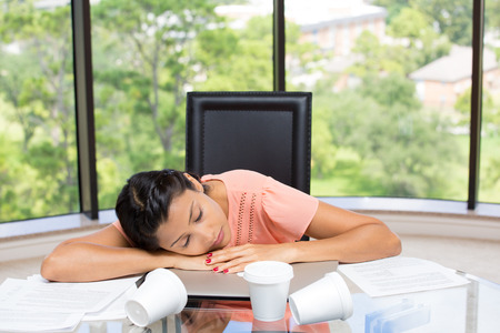 sedentary: Closeup portrait of a tired, exhausted businesswoman sleeping, resting on laptop,empty coffee cups all over, incomplete paperwork, stressed out. Isolated glass window background showing scenery. Stock Photo