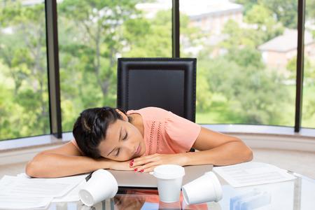 sedentario: Retrato del primer de un cansado, empresaria de dormir exhaustos, descansando en la computadora portátil, tazas de café vacías por todas partes, el papeleo incompleto, estresado. Fondo de la ventana de cristal que muestra aislada paisaje. Foto de archivo