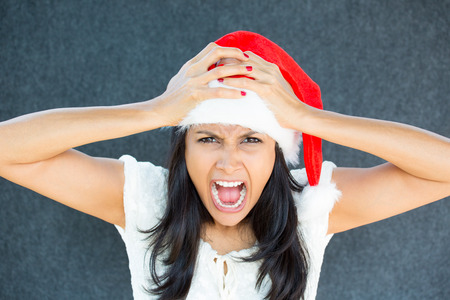 Closeup portrait of a cute Christmas woman with a red Santa Claus hat, white dress, hands on head, stressed out, yelling, showing frustration. Negative human emotions on isolated grey background.